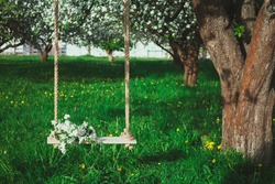 Bouquet of flowers on the tree swing in the blossoming apple orchard