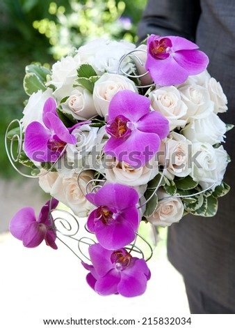 Bouquet of fresh flowers for the wedding ceremony. Bouquet of orchids, roses and other flowers in the groom\'s hands closeup.