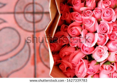 Bouquet of fresh pink roses with pattern pavement background. Floral design, arrangement, flower production, or celebrating of special occasion such as wedding, Valentines or Mother's Day concepts.