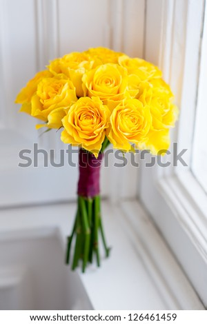 bouquet of fresh yellow roses by a window