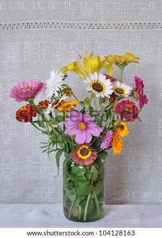Bouquet of garden flowers in a glass jar on the background of an old linen canvas. August, the Central Russia