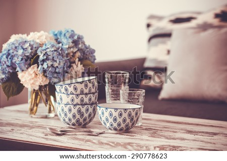 Bouquet of hortensia flowers and glass bowls on modern wooden coffee table and cozy sofa with pillows. Living room interior and home decor concept. Toned image