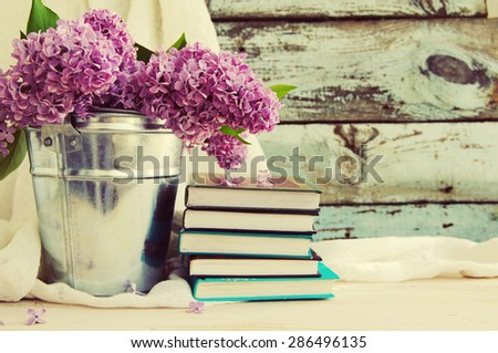 Bouquet of lilac flowers in a metal bucket and a pile of books against an old wooden board, a decor in vintage style