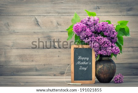 bouquet of lilac flowers in vase on wooden background. blackboard with sample text Happy Mother\'s Day! retro style toned picture