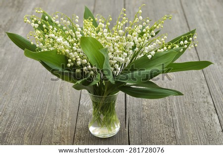 Bouquet of lilies of the valley in glass vase on wooden background