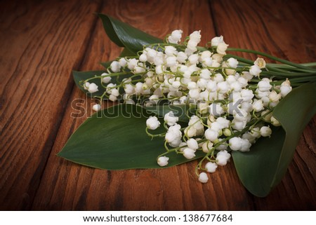 Bouquet of lilies of the valley on a background of wooden boards