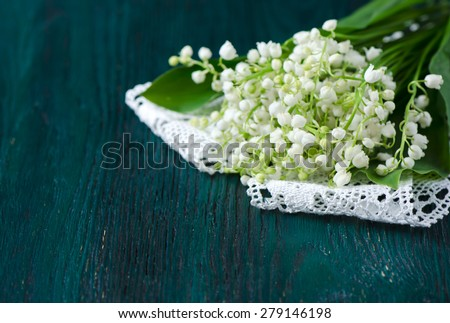 Bouquet of lilies of the valley on a blue wooden table