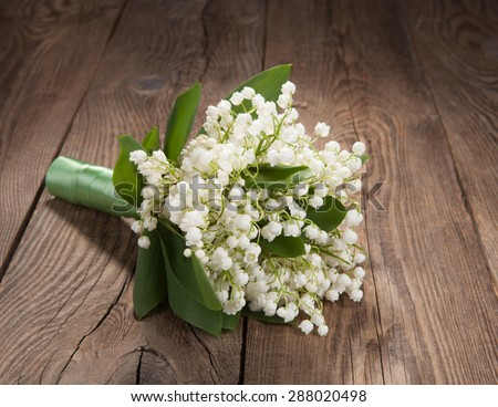 bouquet of lilies of the valley on the old board
