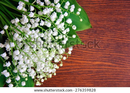 Bouquet of lilies of the valley on the wooden board