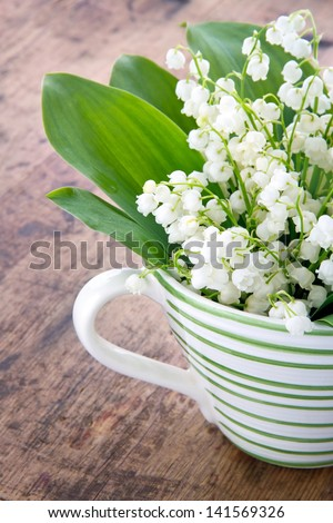 Bouquet of lily of the valley spring flowers in a green striped cup on wooden rustic vintage background