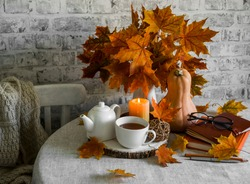 Bouquet of maple leaves, pumpkin, hot tea, lighted candle on the kitchen table.Warm cozy autumn interior