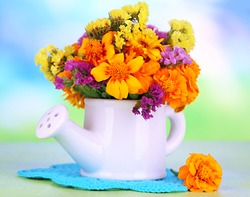 Bouquet of marigold flowers in watering can on wooden table on natural background