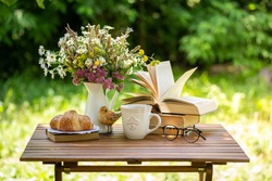 Bouquet of meadow flowers, croissant, cup of tea or coffee, books on table in summer idyllic garden. Rest in garden, reading books, breakfast, vacations in nature concept. Summertime in garden