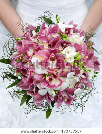 Bouquet of orchids, roses and other flowers in the bride\'s hands closeup. Bouquet of fresh flowers for the wedding ceremony.