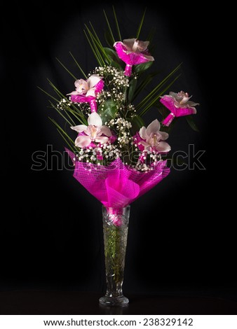 Bouquet of orchids stands in a glass vase on a black background