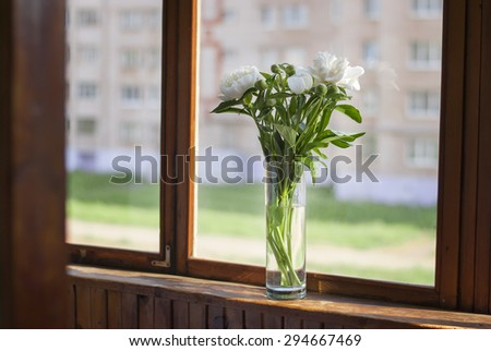 Bouquet of peonies in a glass vase on the window. The sun\'s rays on a wooden window sill, blurred background.