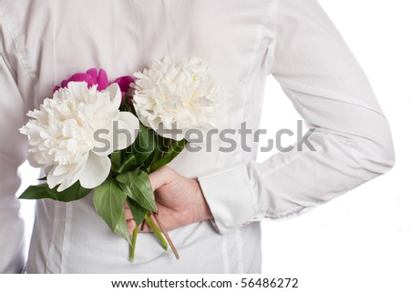 Bouquet of peonies in hand behind the back of the man in white shirt