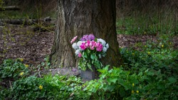 Bouquet of pink and white flowers placed outside in front of a tall oak tree.