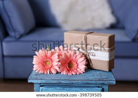 Bouquet of pink gerberas with gift box on blue table, close up