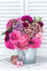 bouquet of pink hydrangea flowers, dahlias and stonecrop in vintage pot