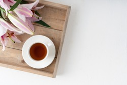 Bouquet of pink lilies on a wooden tray. Pink lilies and a cup of tea on a tray. Pink lilies on a white background.