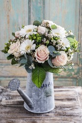 Bouquet of pink roses and white gerbera flowers in grey watering can