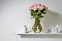 Bouquet of pink roses in a glass figured vase on a white fireplace console. A faience figurine of two pears and a bird as an interior decoration. Copy space. Rose White Pink O'hara.