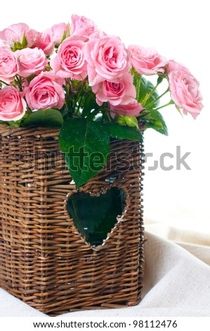 bouquet of pink roses in a wicker basket and linen fabric on a white background