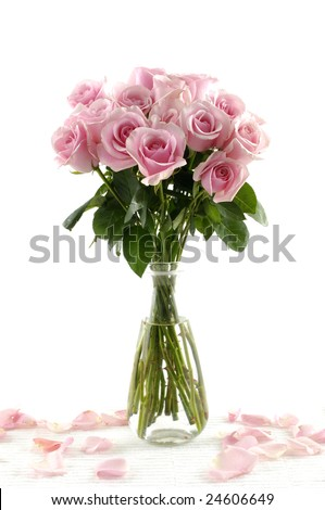 Bouquet of pink roses in glass vase with petals isolated on white