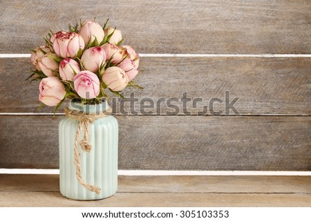 Bouquet of pink roses in turquoise ceramic vase, copy space