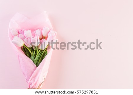Bouquet of pink tulips wrappen in pink paper. - Shutterstock ID 575297851