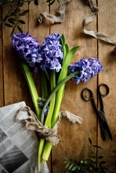 bouquet of purple hyacinth flowers on a wooden background with old vintage scissors. abstract composition with purple flowers. flowers top view
