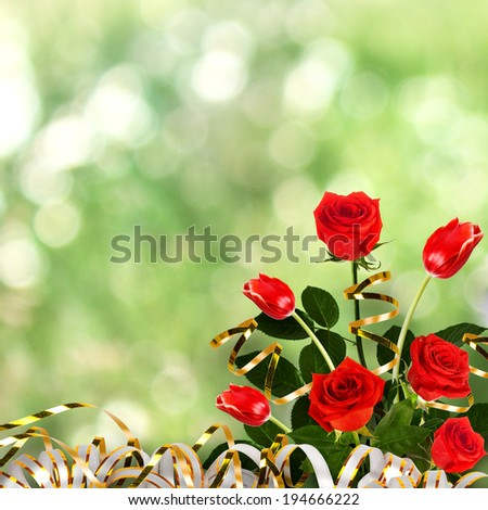Bouquet of red roses and tulips with green leaves and ribbons on the abstract background with bokeh effect