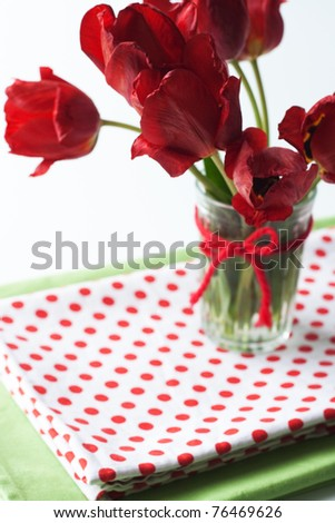 Bouquet of red tulips and a polka dot tablecloth