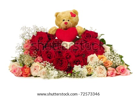 Bouquet of rose flowers isolated on white background. The roses are aranged as a heart shape. A teddy bear is sitting ontop of the flowers.