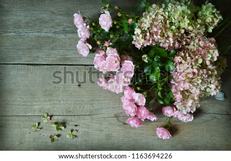 Bouquet of roses and  hydrangea on wooden background. Greeting card #1163694226