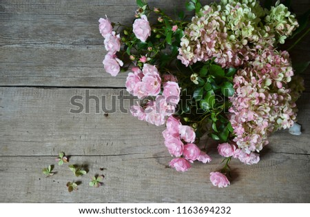 Bouquet of roses and  hydrangea on wooden background. Greeting card #1163694232
