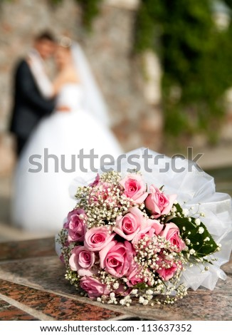 bouquet of roses lies on the background of the bridegroom and of the bride