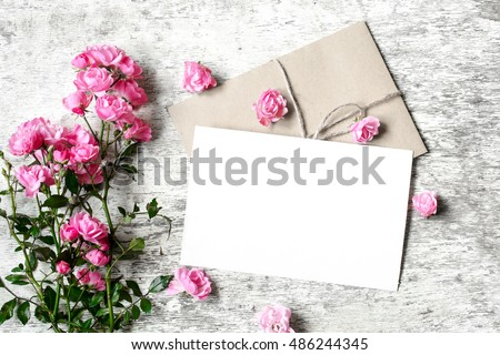 Bouquet of roses with a blank greeting card and envelope on white rustic wooden background with copy space #486244345