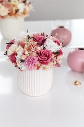 Bouquet of stabilized flowers in a white ceramic vase at home on the dressing table. Interior decor.
