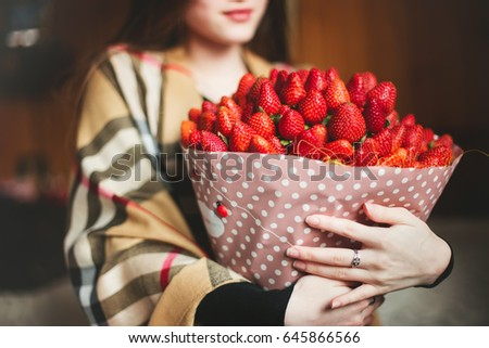 Bouquet of strawberries close-up in the hands of a girl #645866566