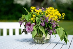 Bouquet of summer flowers freshly picked from the garden in a vase on a white wooden table outdoors in the garden