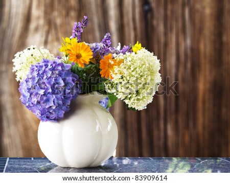 Bouquet of summer flowers in a vase before wooden background