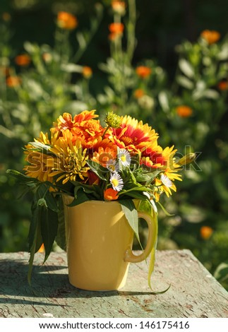 Bouquet of summer flowers in a yellow mug