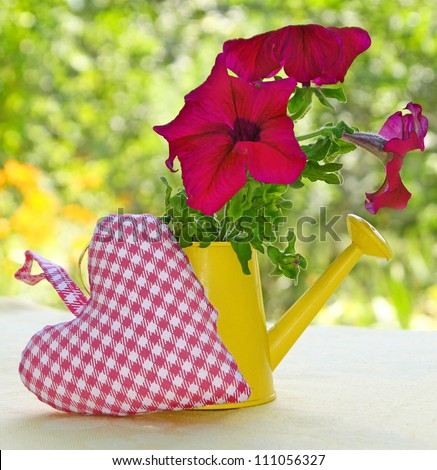 Bouquet of summer flowers is in a yellow watering-can and heart