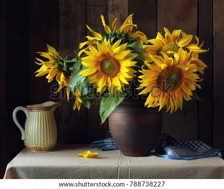Bouquet of sunflowers in a clay jug on the table on the wooden background. Still life in rustic style.