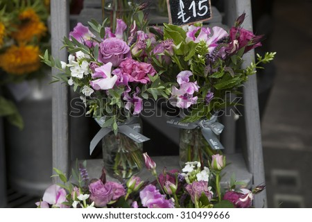 bouquet of Sweet pea, Lathyrus odoratus, flowers in a purple vase standing on wooden grey steps
