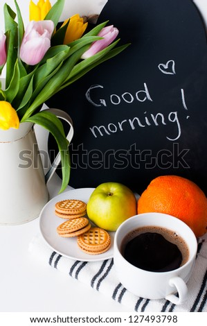 bouquet of tulips in a white jug, morning coffee, fruit and chalk board with the inscription on a white background