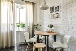Bouquet of tulips in interior of the kitchen in Scandinavian style with white furniture and a dining table. All photos in photo frames on whall made by me.