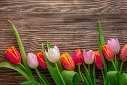 Bouquet of tulips on a wooden rustic table. Spring holidays concept background.